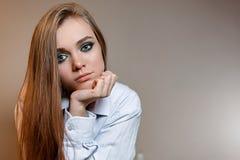 Ledsen flicka i skjorta på grå bakgrund arkivbilder