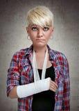 Ledsen flicka med en bruten arm Arkivfoton