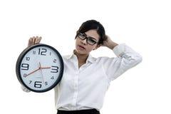 Ledsen flicka med en stor klocka i händer arkivfoton