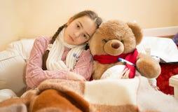 Ledsen flicka med influensa som ligger i säng med nallebjörnen Royaltyfri Bild