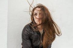 Ledsen flicka med långt hår i läderomslag arkivfoton