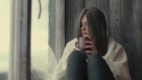 Ledsen flicka nära fönster som tänker om något stock video