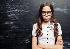 Ledsen flicka nära svart tavla arkivbild
