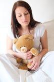 Ledsen flicka som får ensam och kramar den mjuka nallebjörnen arkivfoton