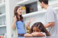 Ledsen flicka som lyssnar till hennes argumentera för föräldrar Arkivfoto