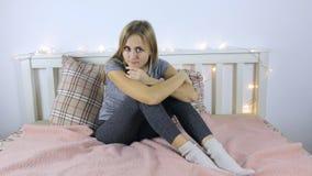 Ledsen flicka som sitter på säng arkivfilmer