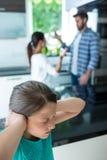 Ledsen flicka som täcker henne öron medan föräldrar som argumenterar i bakgrund Arkivbild