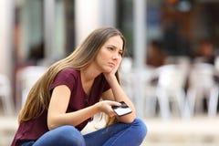 Ledsen flicka som väntar på en mobiltelefonappell arkivbild