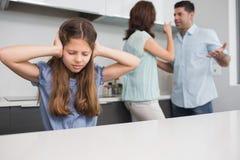 Ledsen flickabeläggning gå i ax medan föräldrar som grälar i kök Royaltyfri Bild