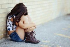 Ledsen flickasitng vid tegelstenväggen Arkivfoton