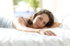 Ledsen flickvän som missa hennes pojkvän på sängen arkivfoton