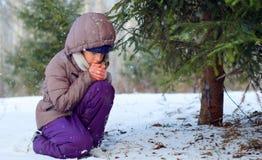Ledsen frysa flicka som försöker att bli varmt i vinterskog Royaltyfri Fotografi