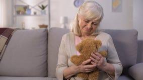Ledsen gammal kvinna som kramar leksaknalle-björnen, saknade barnbarn, långt avskiljande lager videofilmer