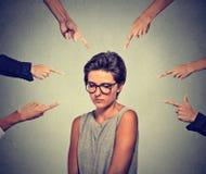 Ledsen generad kvinna i exponeringsglas som ser ner många fingrar som pekar på henne Arkivbild