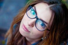 Ledsen härlig flicka i exponeringsglas med blåa ögon Arkivfoton