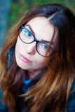 Ledsen härlig flicka i exponeringsglas med blåa ögon Arkivbild