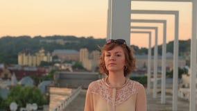 Ledsen härlig stilfull ung kvinna som går på stadsbron och tänker om liv lager videofilmer