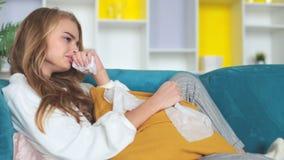 Ledsen hållande ögonen på television för ung kvinna på en soffa och gråta arkivfilmer