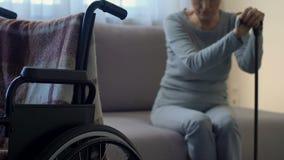 Ledsen hög dam som ser rullstolen och att känna sig ensamt och övergett, fördjupning lager videofilmer