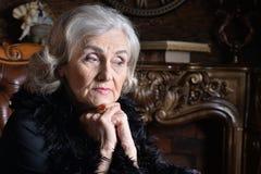 Ledsen hög kvinna i boaen som hemma poserar royaltyfria bilder