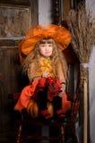 ledsen halloween häxaflicka i dräkt med kvasten royaltyfria foton