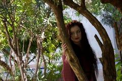 Ledsen hippieflicka som lutar mot träd royaltyfri bild