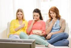Ledsen hållande ögonen på tv för tonårs- flicka tre hemma Royaltyfri Fotografi