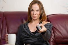 Ledsen irriterad ung kvinna som hemma använder tvfjärrkontroll Arkivfoton