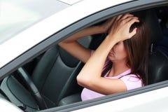 Ledsen kvinna i en bil arkivfoto