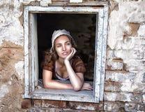 Ledsen kvinna i en lantlig klänning som sitter nära fönster i gamla den ensamma huskänseln Cinderella stil Arkivfoton
