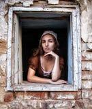 Ledsen kvinna i en lantlig klänning som sitter nära fönster i gamla den ensamma huskänseln Cinderella stil Arkivbild