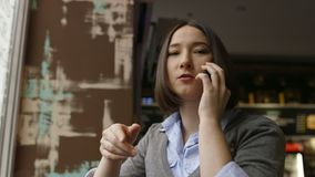 Ledsen kvinna i hemtrevligt kafé genom att använda smartfone stock video