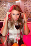 Ledsen kvinna i kök med exponeringsglas av wine Royaltyfri Fotografi