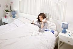 Ledsen kvinna i många säng med näsduken som känner det sjuka sned bollskottet Fotografering för Bildbyråer