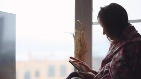 Ledsen kvinna i plädsammanträde på en fönsterfönsterbräda som ser i fönster, medan genom att använda mobiltelefonen 1920x1080 arkivfilmer