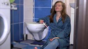 Ledsen kvinna i pyjamas som ser graviditetstestet som sitter nära garderoben i badrum arkivfilmer