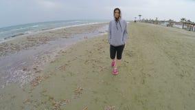 Ledsen kvinna i sportswear som promenerar stranden och tänker om pojkvän arkivfilmer