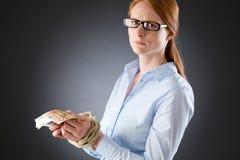 Ledsen kvinna med bundna händer som rymmer pengar Royaltyfri Foto