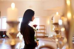 Ledsen kvinna med den röda rosen på begravningen i kyrka Arkivfoton