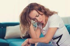 Ledsen kvinna med en hand på det head sammanträdet på en soffa i vardagsrummet hemma royaltyfri fotografi