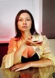 Ledsen kvinna med exponeringsglas av konjak Arkivbild