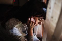 Ledsen kvinna med hennes huvud ner att se till och med fönstret arkivfoton