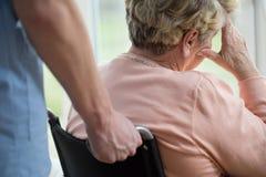 Ledsen kvinna på rullstolen royaltyfria foton