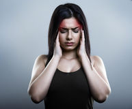 Ledsen kvinna som har migrän eller huvudvärk Royaltyfri Foto