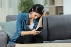 Ledsen kvinna som kontrollerar det smarta telefoninnehållet arkivbild