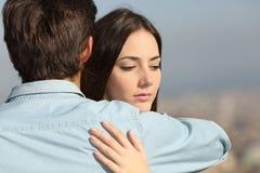 Ledsen kvinna som kramar hennes pojkvänparproblem Royaltyfri Foto