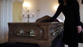 Ledsen kvinna som sätter den röda rosen in i kistan på begravningen lager videofilmer