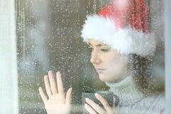 Ledsen kvinna som ser till och med ett fönster i jul royaltyfria bilder