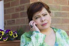 Ledsen kvinna som utomhus talar på telefonen Royaltyfri Foto