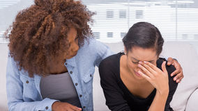 Ledsen kvinnagråt bredvid hennes terapeut Arkivbild